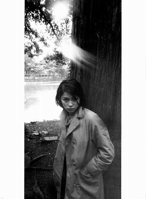 大木の前に立つトレンチコートを着たひし美ゆり子の画像